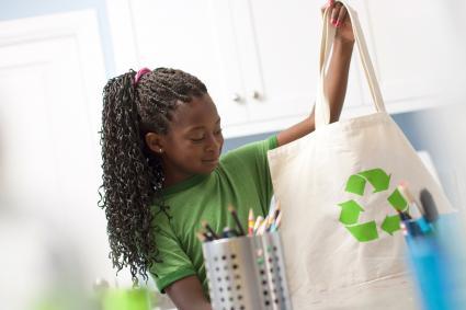 Niña lleva una bolsa con una etiqueta de reciclaje