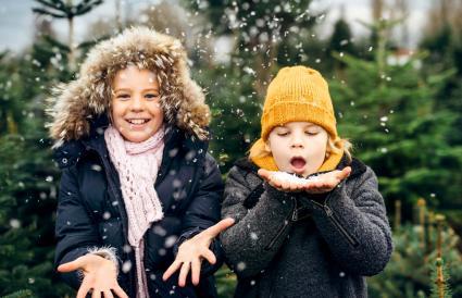 Hermano y hermana divirtiéndose con la nieve