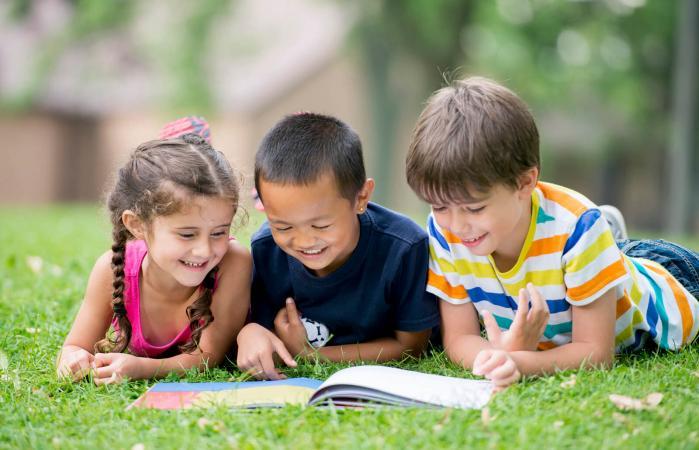 Niños leyendo un libro en el parque