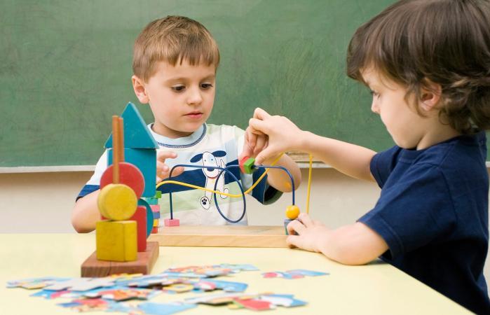 Dos chicos jugando con un juego de alambre de zumbido