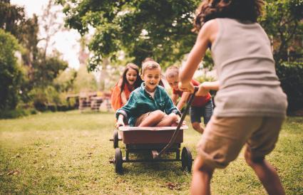 Niño pequeño en un carrito empujado y tirado por amigos