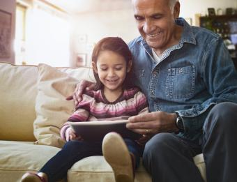 Grandfather and granddaughter on sofa using tablet