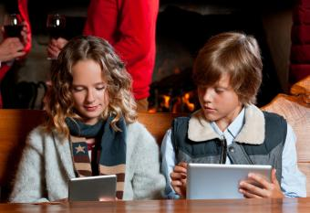 Brother and sister playing on tablets at holiday party