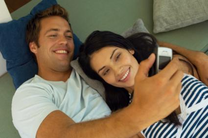 Young couple on sofa taking selfie