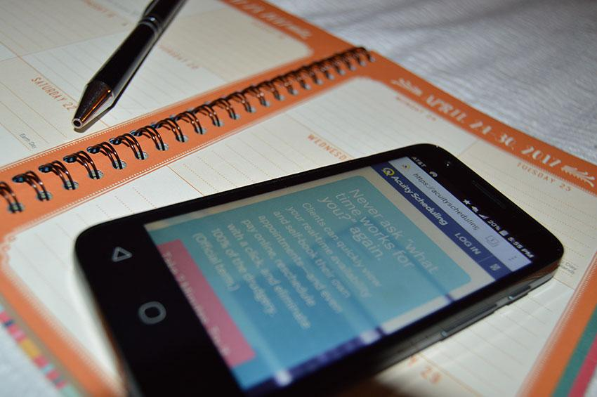 Smartphone laying on an appointment schedule book