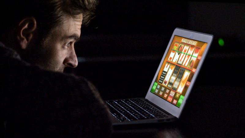 Man Playing Game On Laptop