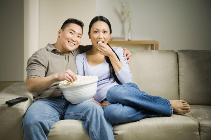 Couple sitting on sofa watching drama