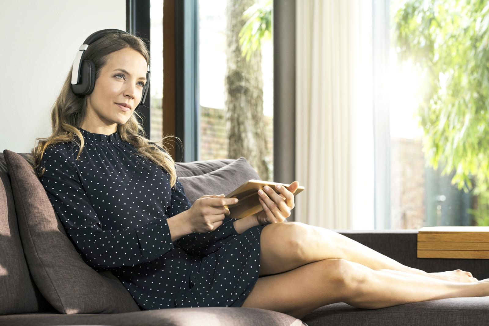 Woman with tablet and headphones relaxing on couch at home