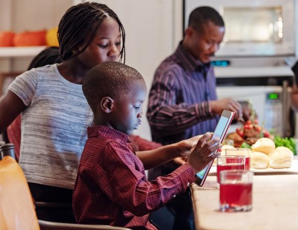 Boy playing game on tablet and dad preparing thanksgiving dinner