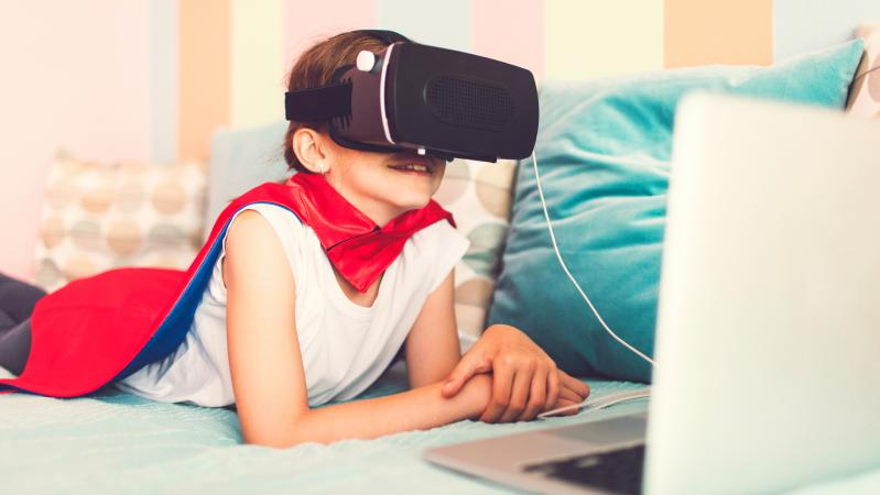 Girl laying on the bed and wearing superhero cape playing video games