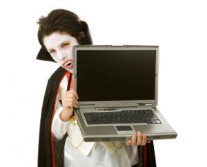 Boy dressed as vampire holding laptop