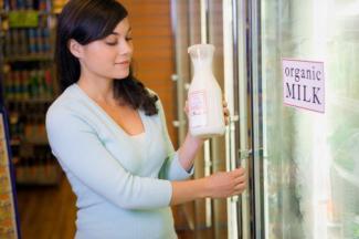 Woman shopping for organic milk