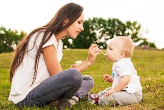 Mother feeding her baby organic puree