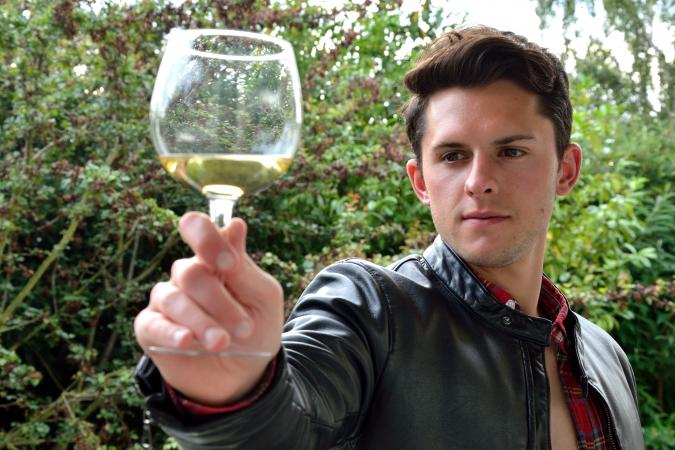 man inspecting a glass of wine