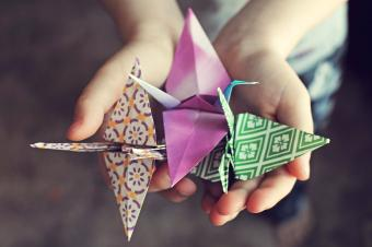 Boy holding three hand made origami cranes