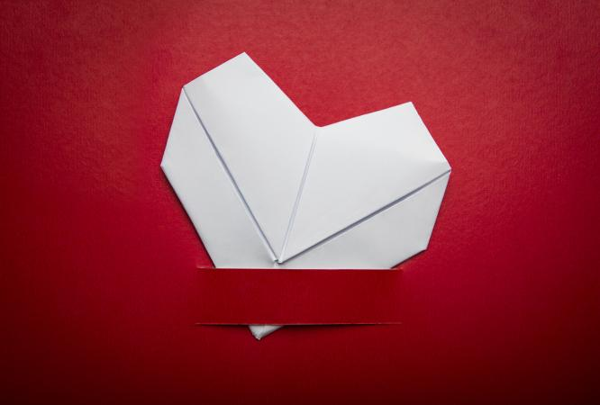 origami folded heart on red background