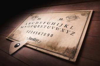 Ouija board planchette pointing to goodbye