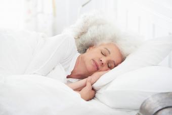 sleeping senior woman in white bed