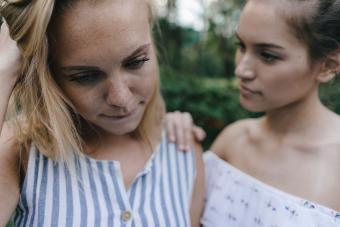 Young woman comforting sad female friend