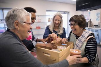 volunteers packing soup containers into crate