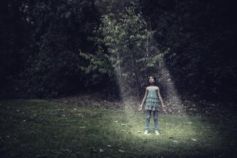 Girl standing in a light beam