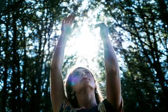 Woman reaching toward sky