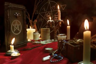 Burning candles, magic book, quill, jewellery, chalk and pentagram symbol