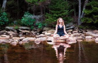 Woman meditating in forest by a stream