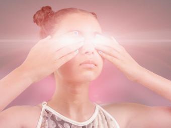 girl covering glowing eyes