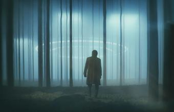 Man in the forest at night with landing UFO