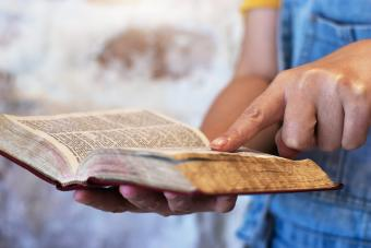 Person's hands held over a bible