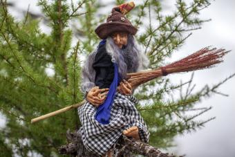 Plastic doll witch with a broom in the forest