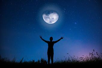 Woman looking at the full moon in the night when the sky is full of stars