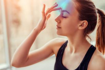 female touching chakra on forehead