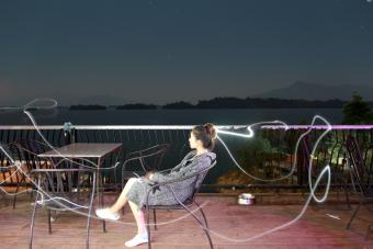 Light Painting and Woman Sitting On Chair At Table Against Sky At Night