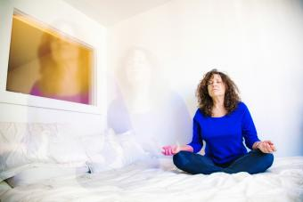 Woman practicing astral projection on her bed