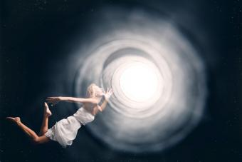 Spirit Woman Floating Into A Tunnel Of Light