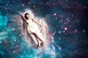 Young woman sleeping on a deck chair floating through the universe