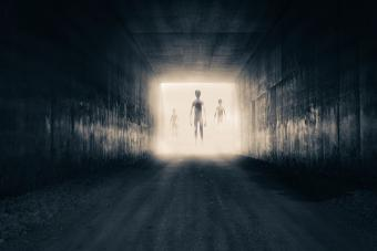 Aliens emerging from the light at the end of a dark sinister tunnel