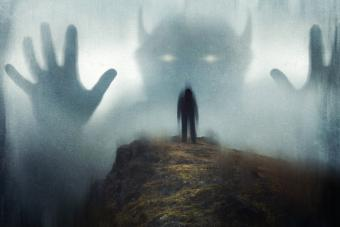 Man looking up at a huge ghostly horned demon appearing out the mist