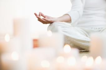 woman meditating in lotus position near lit candles