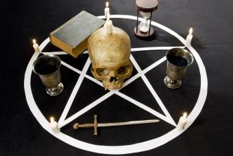 Pentagram/ Pentacle with candles and Human scull on velvet background