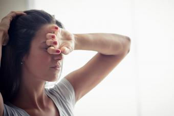 woman holding one hand on forehead