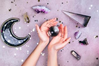 Hands with rings on fingers are holding crystal ball near esoteric set