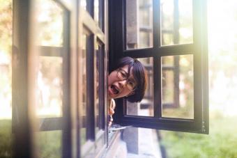Portrait Of Young Woman Shouting From Window