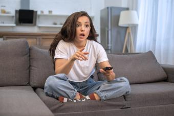 Young woman shocked while watching TV