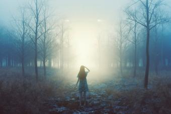Woman in the forest with mysterious lights at night