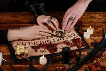 People conducting a seance using a Ouija Board