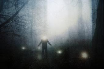 Figure with a glowing head with glowing orbs in a spooky forest