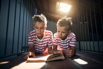 Twins reading a scary book on the attic